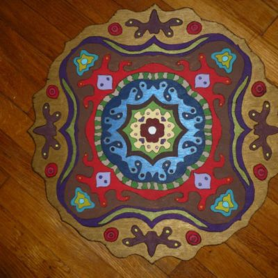 Mandala: This mandala was first drawn on tracing paper and transferred to plywood. The exterior shape was cut with a jigsaw, and the design was painted with acrylic paint. The edges of the design were traced with a wood burner, and the whole thing was finished with a mix of stain and poly.